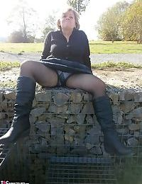 Horny old Caro outdoors in boots spreading pussy to toy with wine bottle
